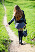 Woman walking on a footpath in the park — Stock Photo