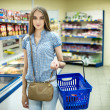 Beautiful young woman shopping for diary products at a grocery store supermarket — Stock Photo #47093641
