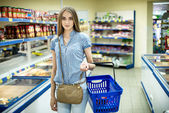 Beautiful young woman shopping for diary products at a grocery store supermarket — Stock Photo