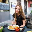 Portrait of a young attractive woman eating salad at street cafe table — Stock Photo #47720603
