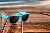 Sunglasses on wooden desk at the summer beach vacation — Stock Photo
