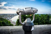 Binocular next to the waterside promenade i looking out to the city and river — Стоковое фото