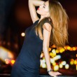 Sexy young beautiful woman posing over night city background — Stock Photo #50741415