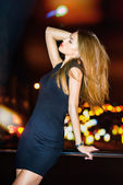 Sexy young beautiful woman posing over night city background — Stock Photo