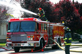 Firemen and fire truck at an apartment fire — Stock Photo