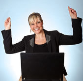 Studio portrait of a cute blond girl with a computer hands up — Stock Photo