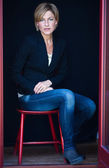 Kobieta siedzi na krześle — Zdjęcie stockowe