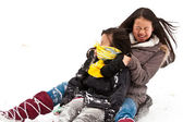 Two sisters sledging holding each other — Stock Photo