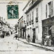 Old postcard of Arpajon, main street and carries from Paris — Stock Photo