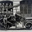 Old postcard of group of firemen on truck — Stock Photo #22022539