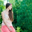 Young pretty teenage girl sitting against green leaves backgroun — Stock Photo #12804755