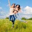 Two happy young women jumping — Foto Stock