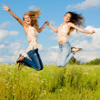 Two happy young women jumping — Stock Photo #12887089