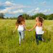 Two happy young women running on green field under blue sky — Stock Photo