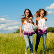 Two happy young women running on green field under blue sky — Stock Photo #13143430