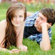 Young happy couple mand womlying on green lawn and smiling — Stock Photo #14411429