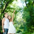 Young happy couple man and woman embracing in green park and poi — Stock Photo