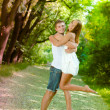 Young happy couple man and woman embracing in green park — Stock Photo