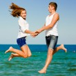 Happy young couple jumping by blue sea over blue sky background — Stock Photo
