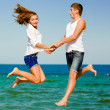 Happy young couple jumping by blue sea over blue sky background — Stock Photo #14772785
