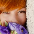 Stock Photo: Young beautiful woman smelling purple chinese rose head shot