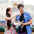 Young couple looking on map in city centre and showing direction - Stockfoto