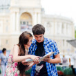 Foto Stock: Young couple looking on map in city centre and showing direction