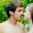 Young happy couple embracing tenderly among green leaves - Stok fotoğraf