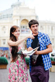 Young couple looking on map in city centre and showing direction — Stock Photo
