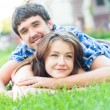 Young happy couple man and woman lying on green lawn and looking — Stock Photo