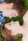 Young happy couple man and woman lying on green lawn — Stock Photo