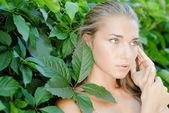 バージニア cr の緑の葉の間で若くてきれいな女性の肖像画 — ストック写真