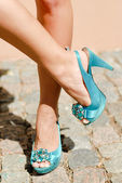 Beautiful woman legs in blue high heel shoes — Stock Photo