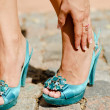 Beautiful woman legs in blue high heel shoes touching ankle in p - Stock Photo