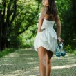 Young beautiful woman walking in green park with shoes in hand - Stock Photo