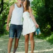 Young happy couple walking in green park holding hands — Stock Photo #15846513