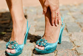 Beautiful woman legs in blue high heel shoes touching ankle in p — Stock Photo