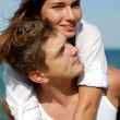 Happy young couple embracing over blue sea and blue sky backgrou — Stock Photo #16852581
