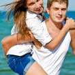 Happy young couple embracing over blue sea and blue sky backgrou — Stock Photo #16852755