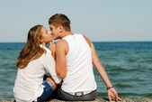 Happy young couple kissing by blue sea over blue sky background — Stock Photo