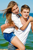Happy young couple embracing over blue sea and blue sky backgrou — Stock Photo