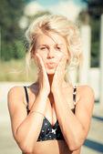 Młody piękny blond kobieta dotyka policzki i umieścić usta w pocałunku — Zdjęcie stockowe