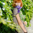 Pretty redhead teenage girl with purple rose by green leaves bac — Stock Photo