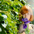 Stock Photo: Pretty redhead teenage girl with purple rose by green leaves bac