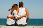Happy young couple sitting by blue sea over blue sky background — Foto de Stock