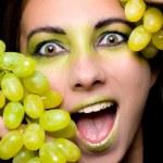 Young beautiful woman holding green grapes closeup — Stock Photo #17864319