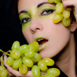 Young beautiful woman holding green grapes closeup — Stock Photo