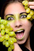 Junge schöne frau, die mit grünen trauben closeup — Stockfoto