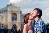 Young happy couple embracing and kissing in city — Stock Photo