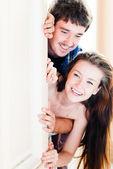 Mladý šťastný pár hledá za rohem a směje se — Stock fotografie